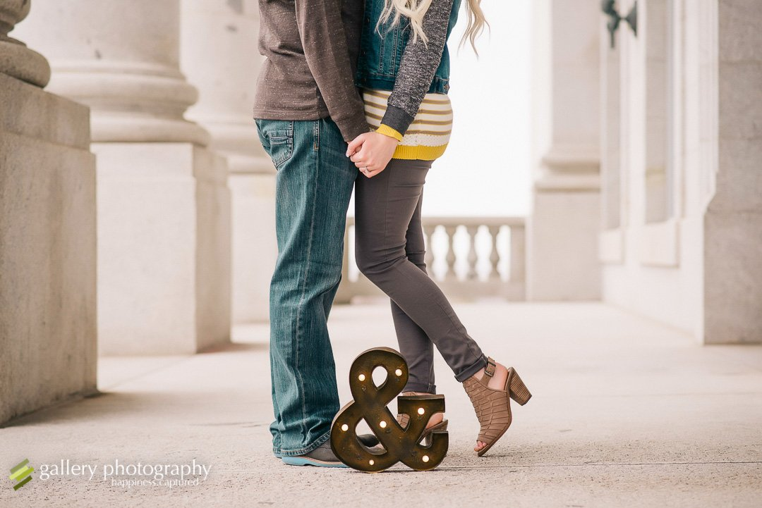 A couple with an ampersand sign at their feet for engagement photography at the Utah State Capitol.