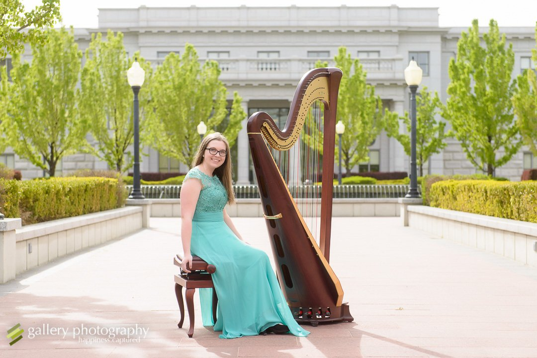 A girl with a harp outside for senior photography at the Utah State Capitol.