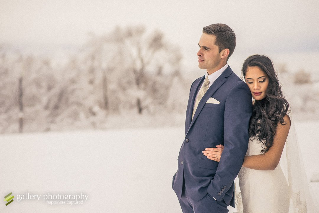 A couple snuggling in the snow with snow covered trees in the background for wedding photography at the Utah State Capitol.