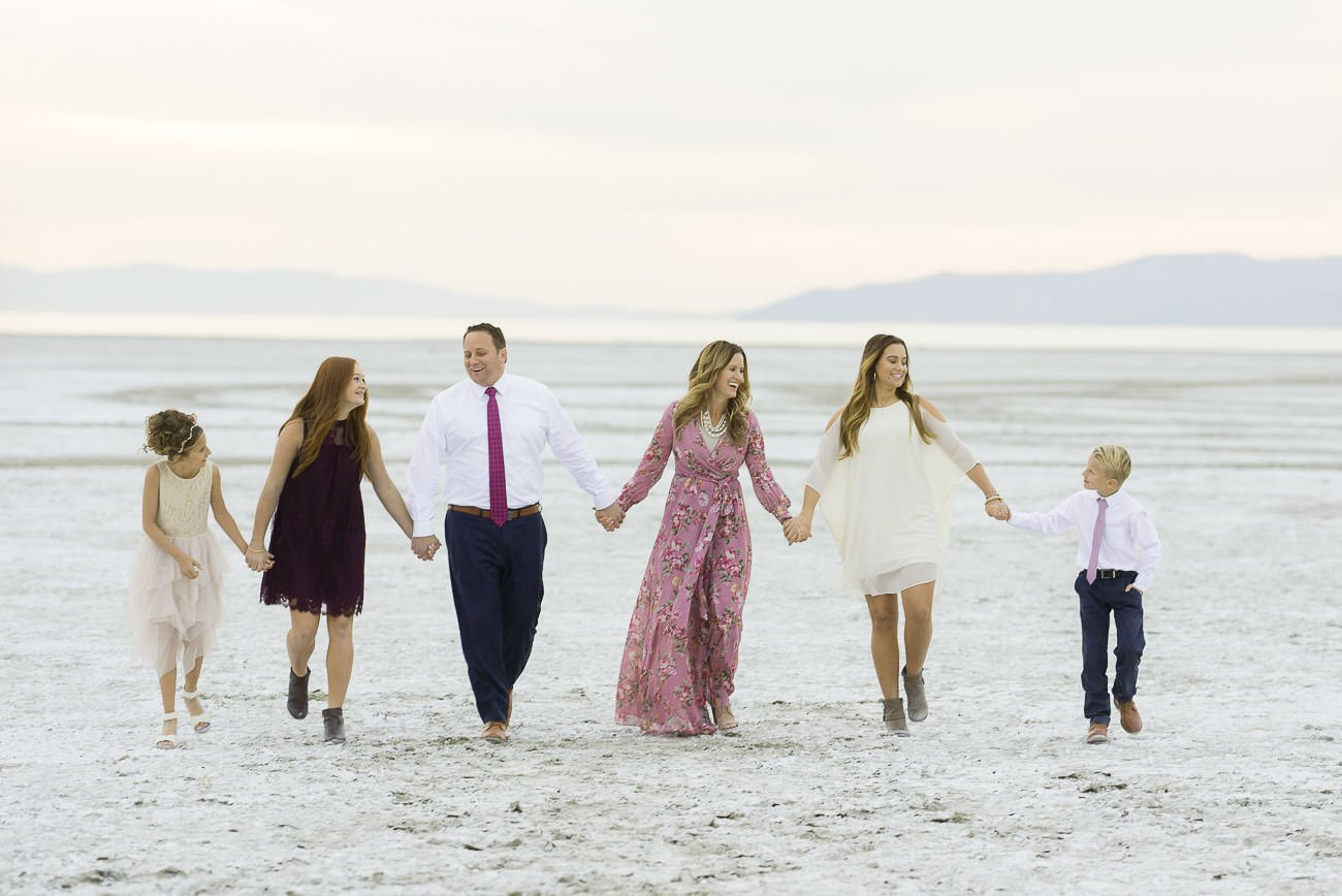 A family walking together holding hands on the beach for Salt Lake City family photography.
