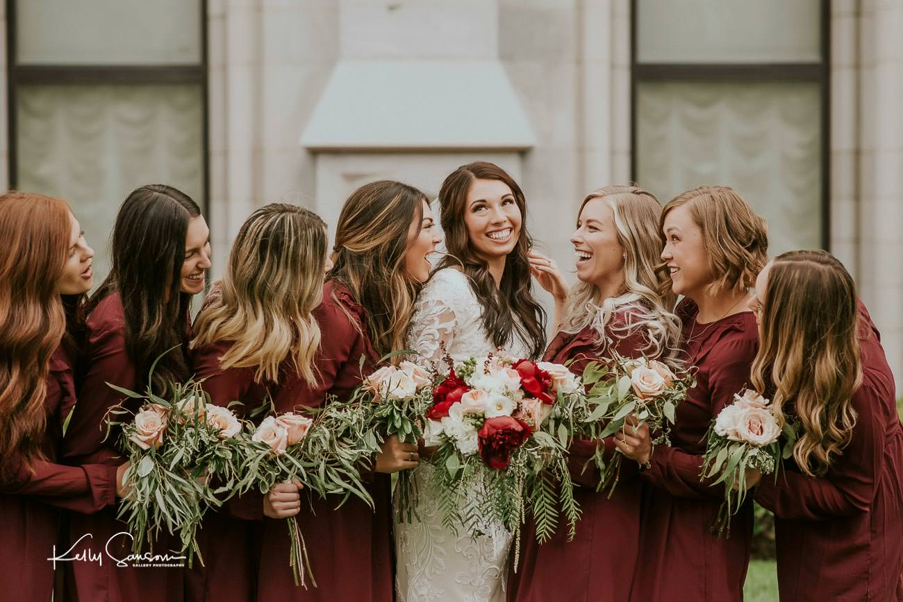 A bride and her bridesmaids talking and laughing by the Salt Lake LDS temple for Salt Lake City portrait photography