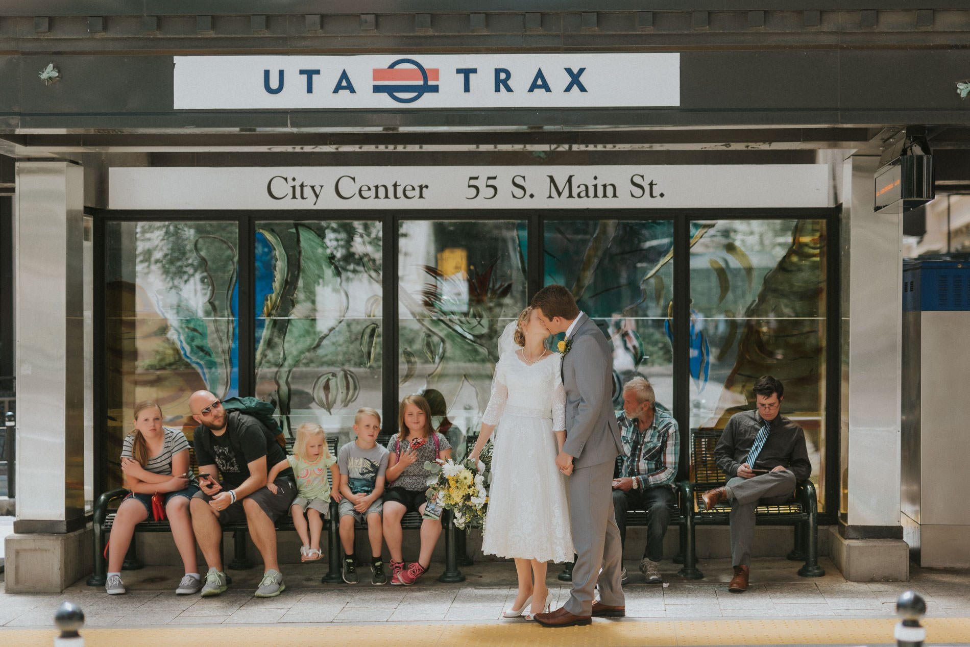 A bride and groom standing at a UTA Trax station kissing for Salt Lake City portrait photography