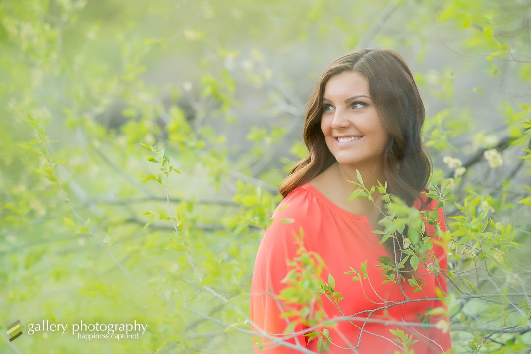 A high school senior girl smiling looking over her shoulder in a spring budding tree for Salt Lake City portrait photography