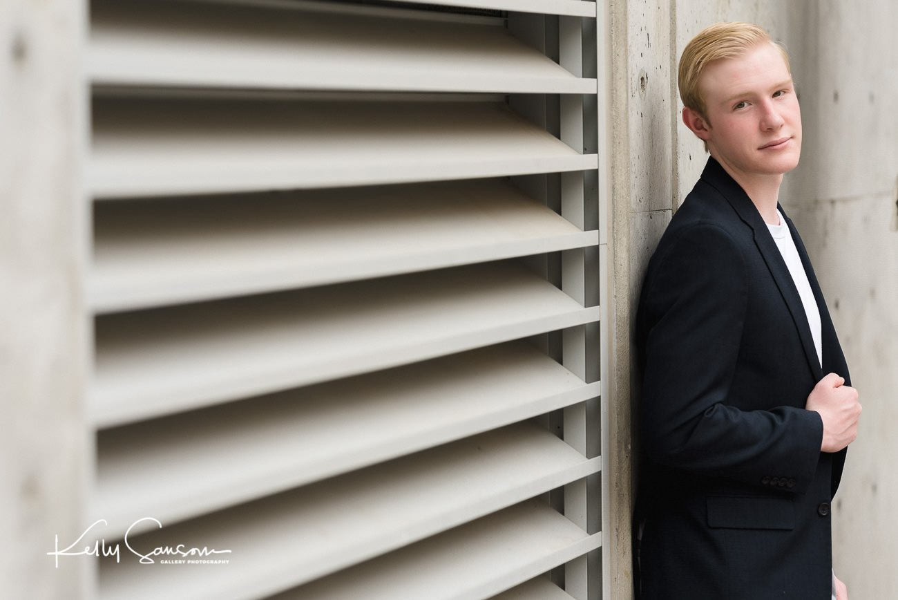 A high school senior stands by an air vent for Salt Lake City senior photography.
