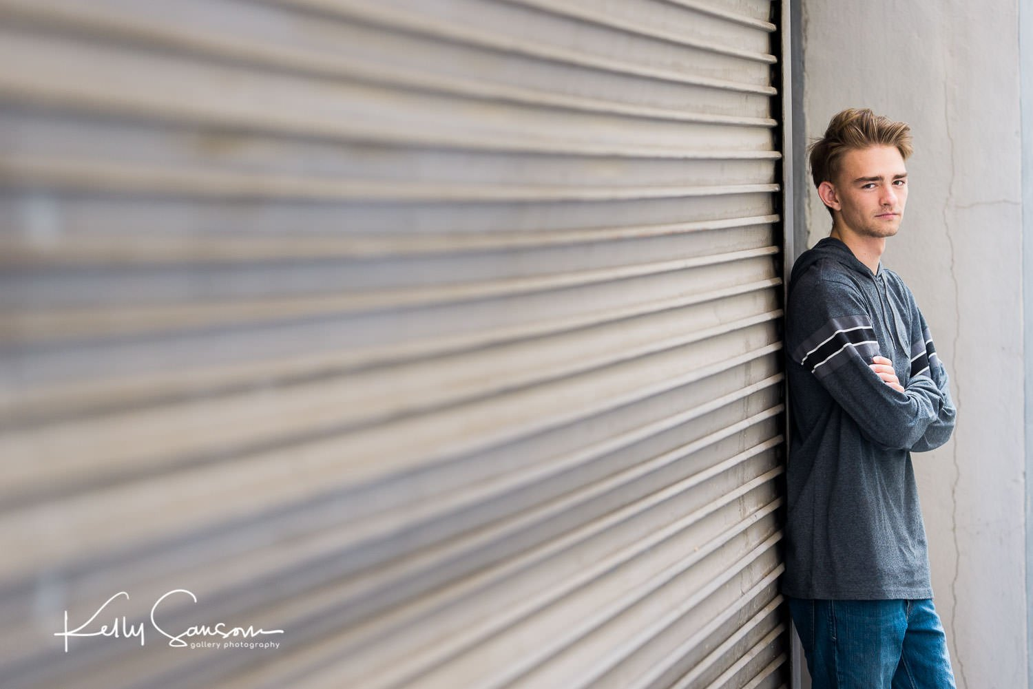 A high school senior stands by a garage door for Salt Lake City senior photography.
