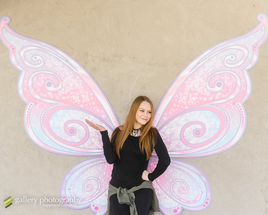 A high school senior stands by painted on wings on a wall for Salt Lake City senior photography.