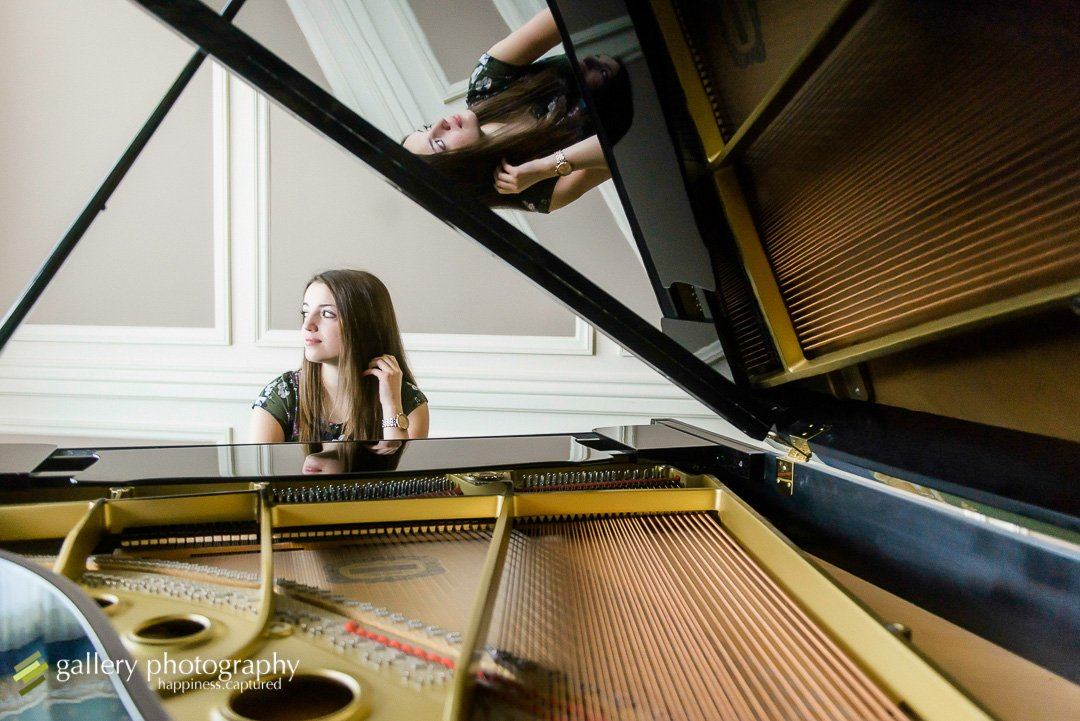 A high school senior girl sits at a piano looking out the window for Salt Lake City senior photography.