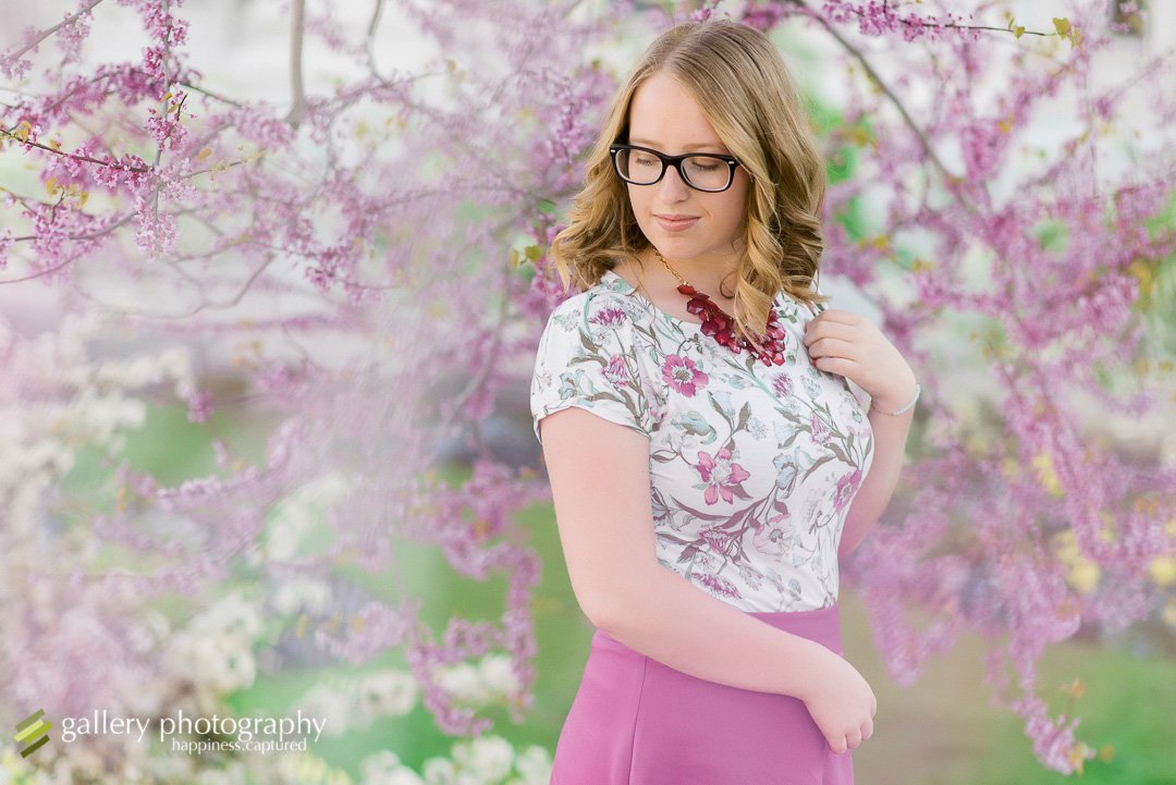 A high school senior girl looks away against a cherry blossom tree for Salt Lake City senior photography.