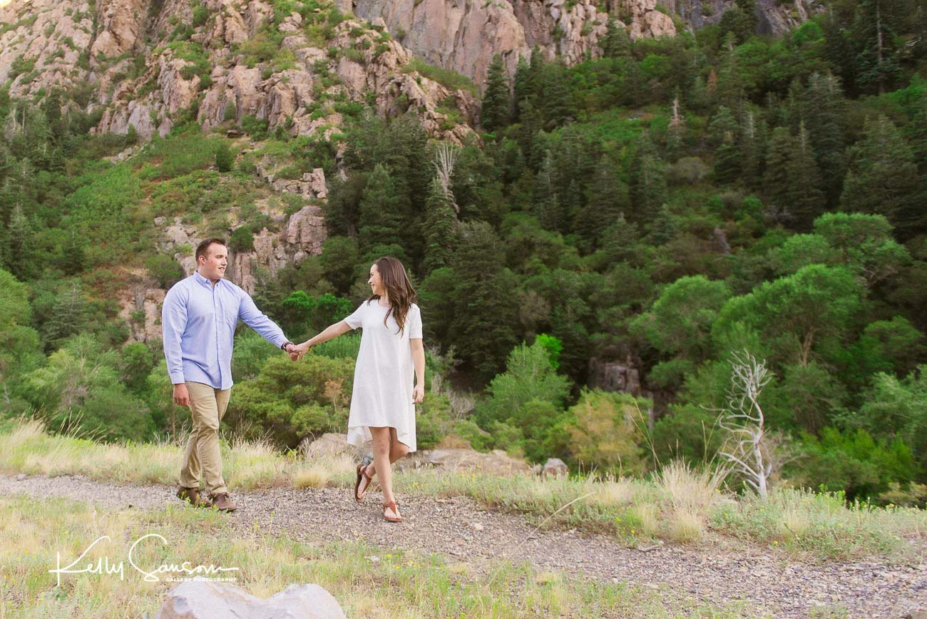 A girl leads her boyfriend along a mountain path for Salt Lake City Utah photography.