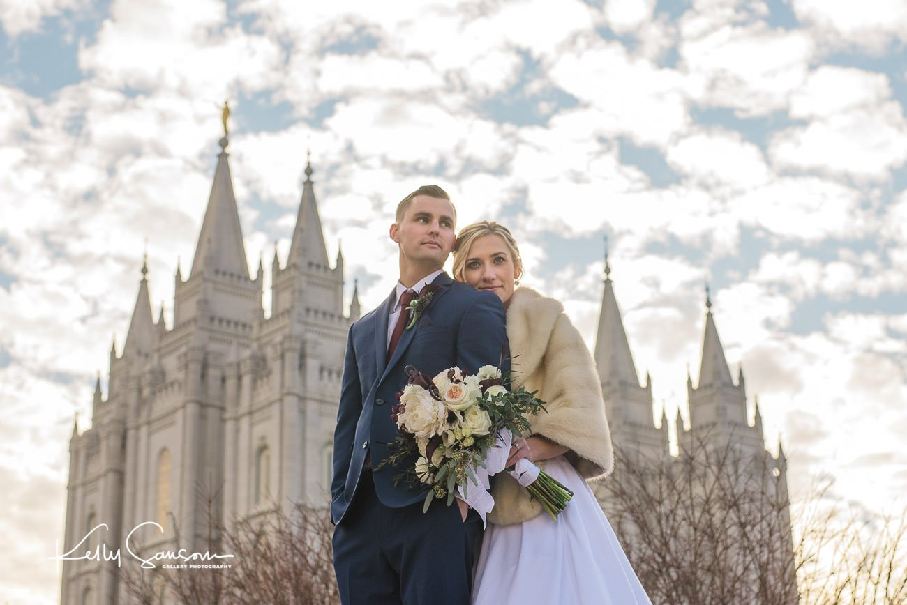 A newlywed couple stands in front of the Salt Lake Temple for Salt Lake City Utah photography.