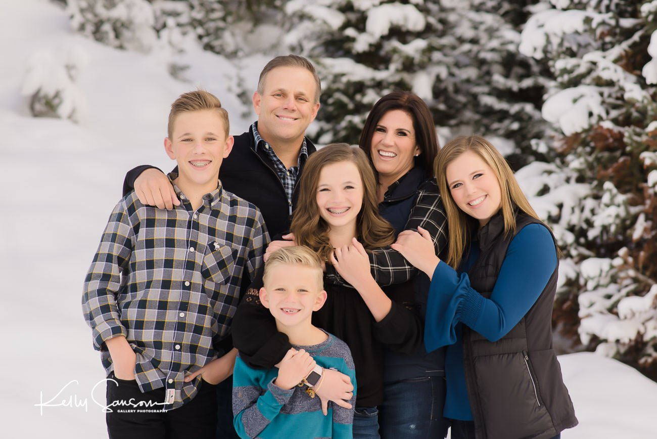 A family snuggles together in front of pines covered in snow for Salt Lake City Utah photography.