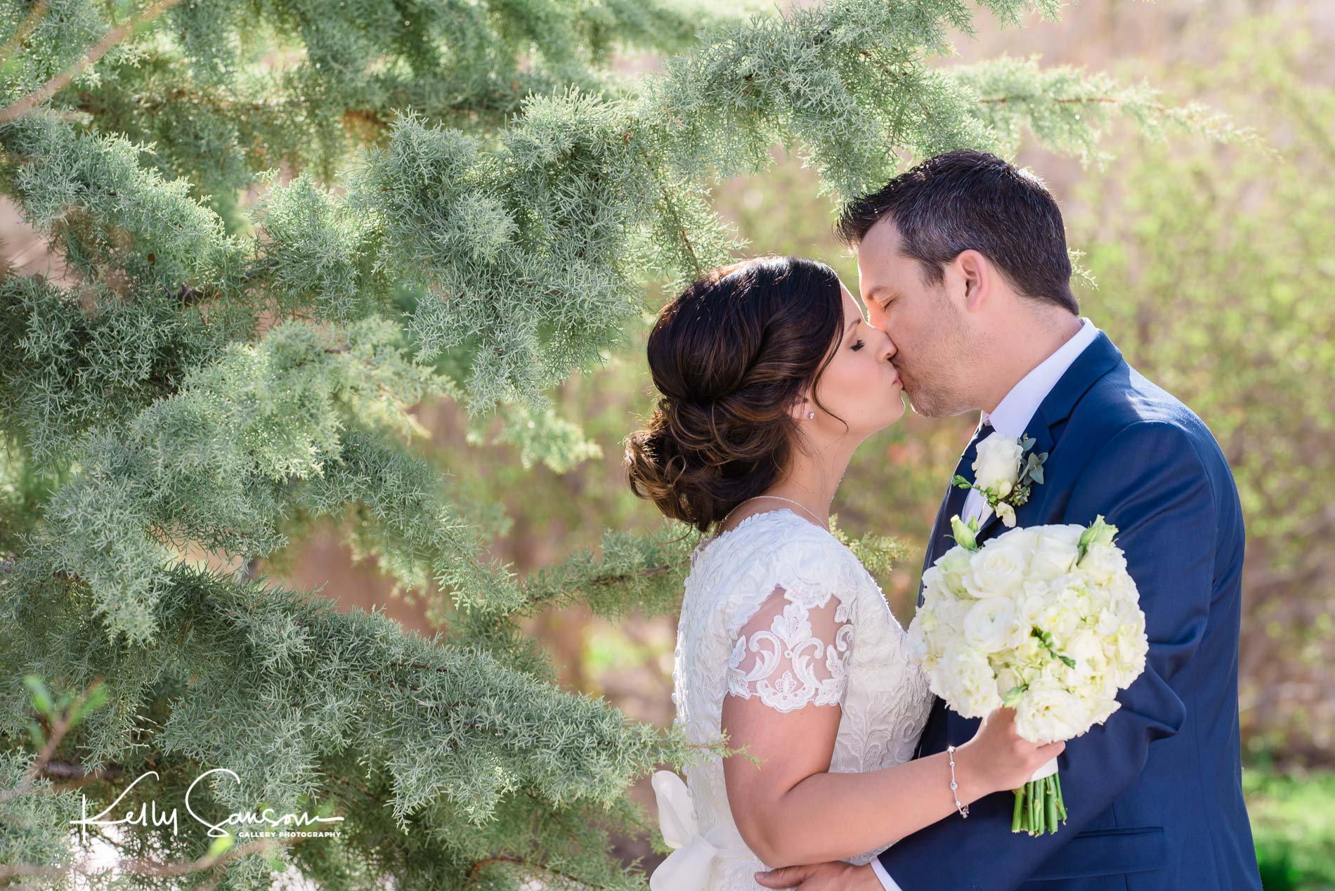 A bride and groom kiss in front of a pine tree for Salt Lake City Utah photography.