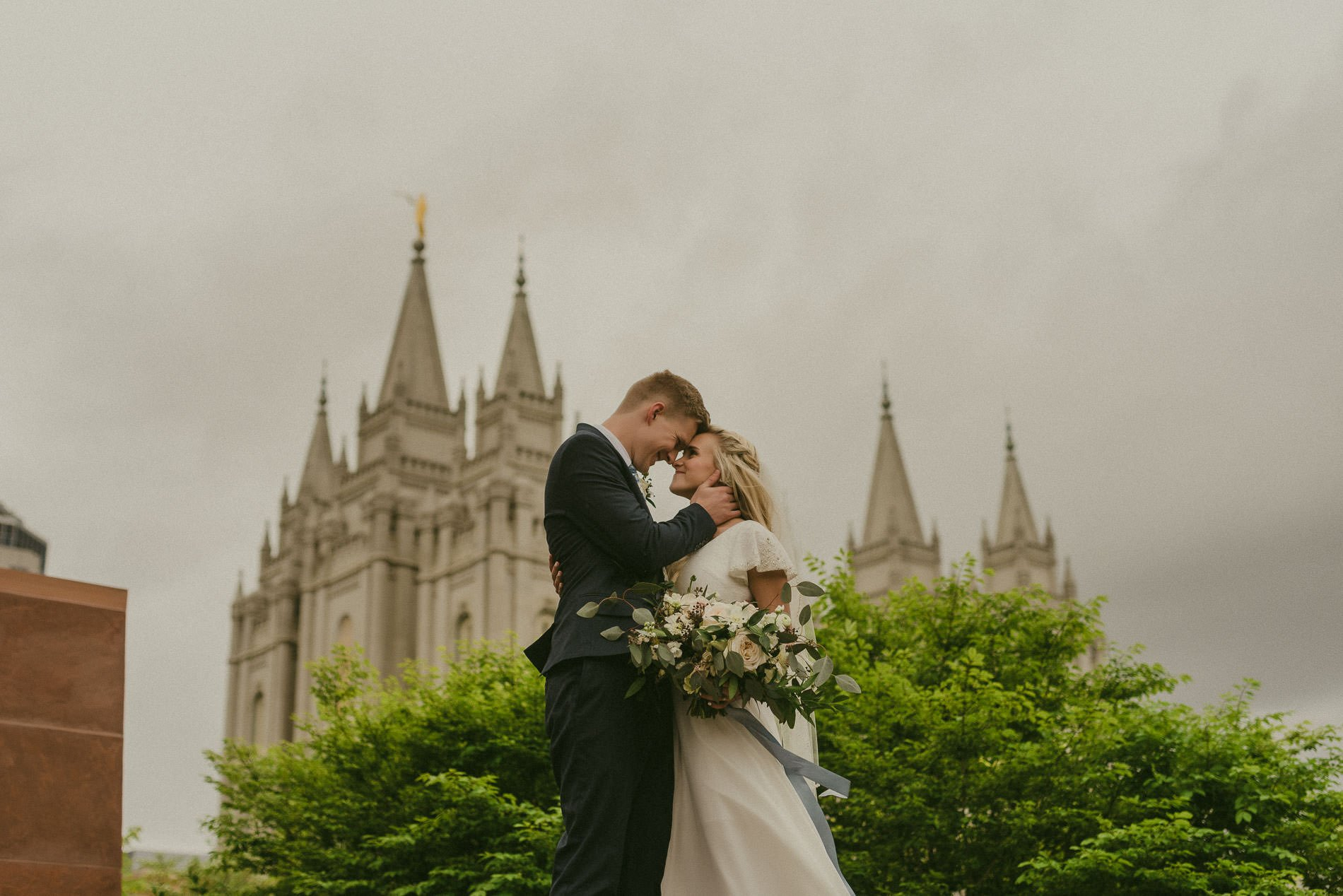 Bride and groom kissing in front of the Salt Lake City LDS Temple for Salt Lake City wedding photography.