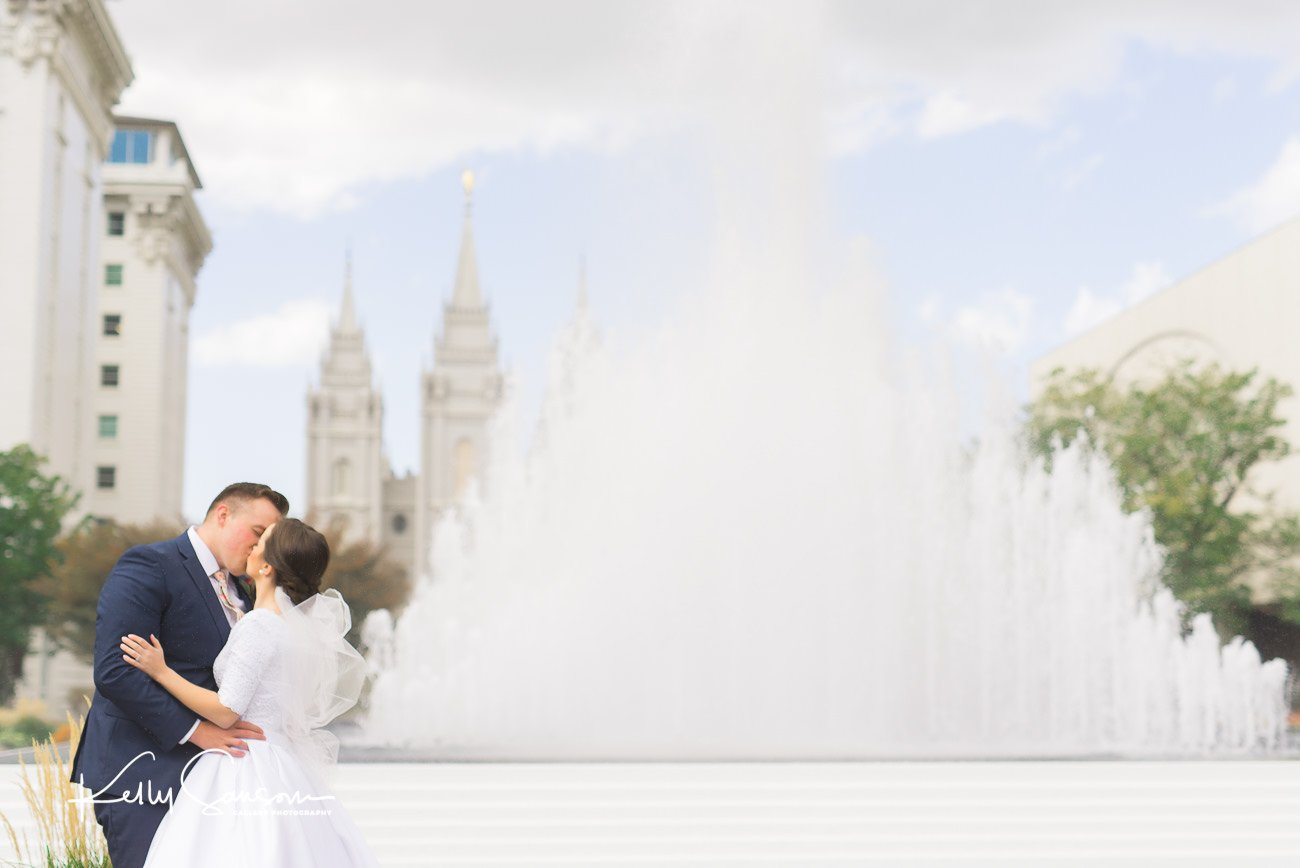 A couple kissing in front of a fountain at the Salt Lake LDS Temple for Salt Lake City wedding photography.