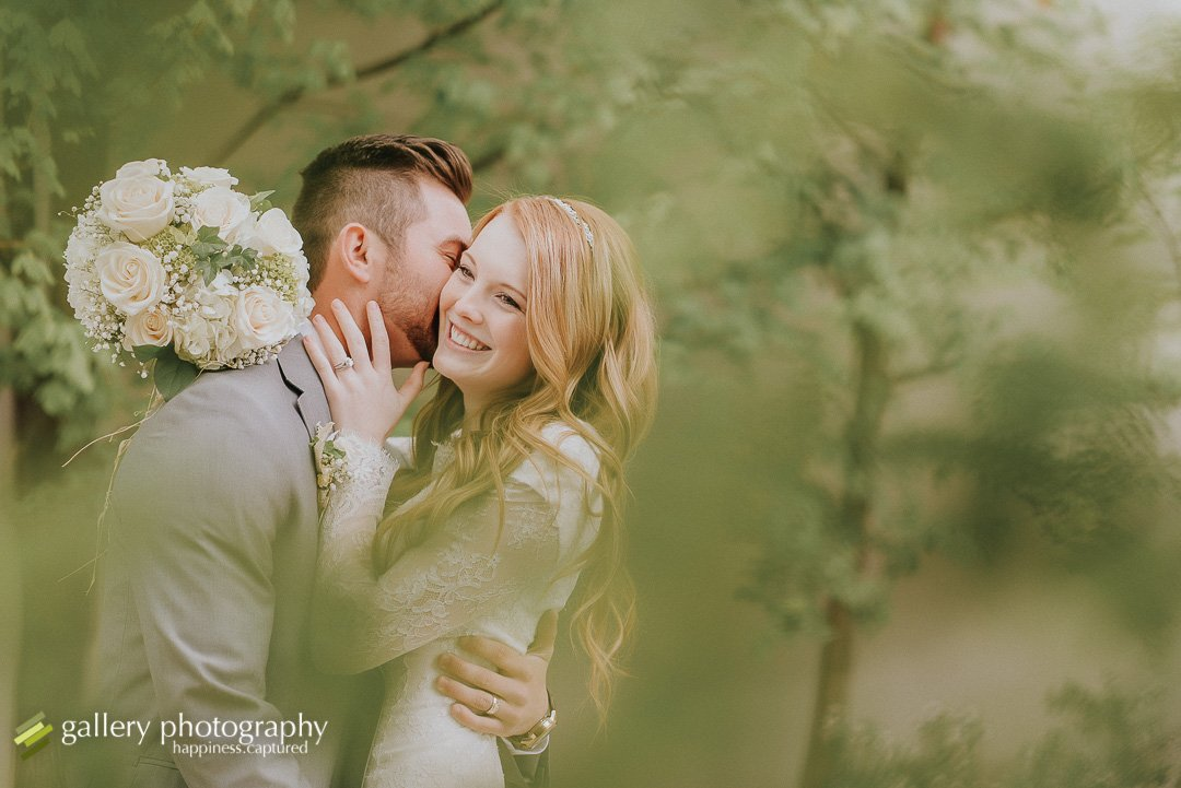 A groom snuggling into his bride in trees for Salt Lake City wedding photography.
