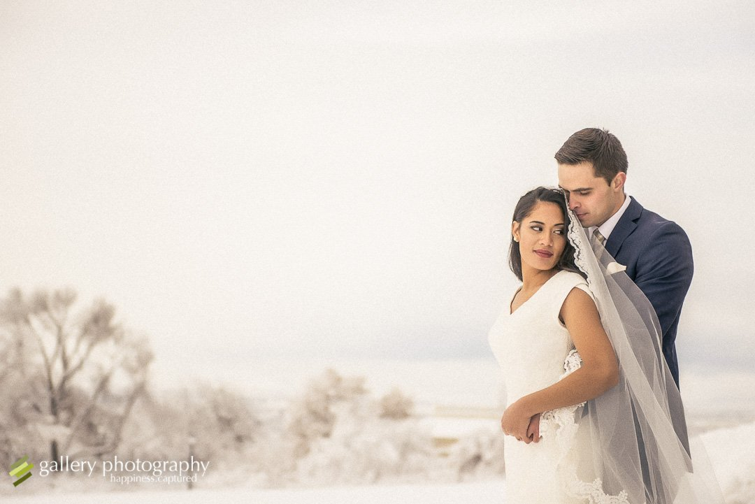 A bride and groom snuggle close with a snowy background for Utah bridal photography.