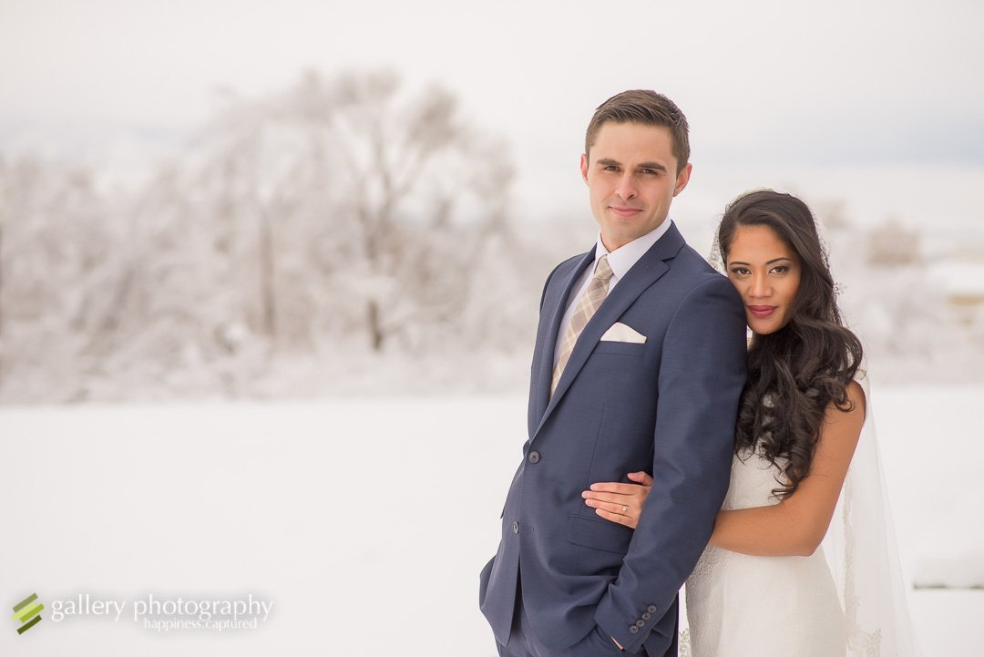 A bride snuggles into the back of a groom in the snow to stay warm for Utah bridal photography.