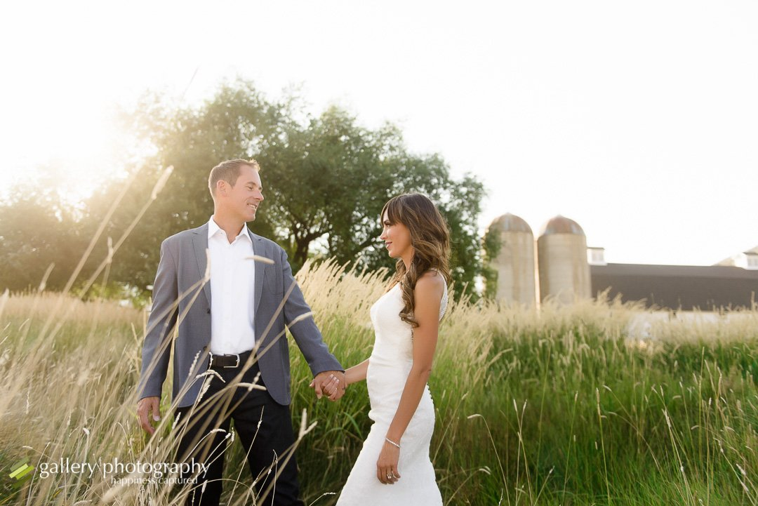 A groom leads a bride in front of grain silos for Utah bridal photography.