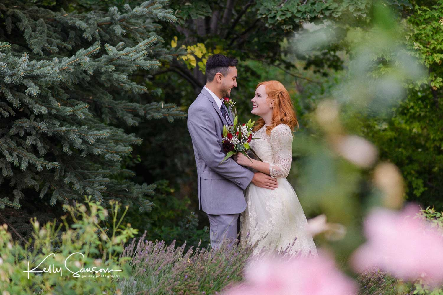 A groom pulls a bride close in front of pine trees for Utah bridal photography.
