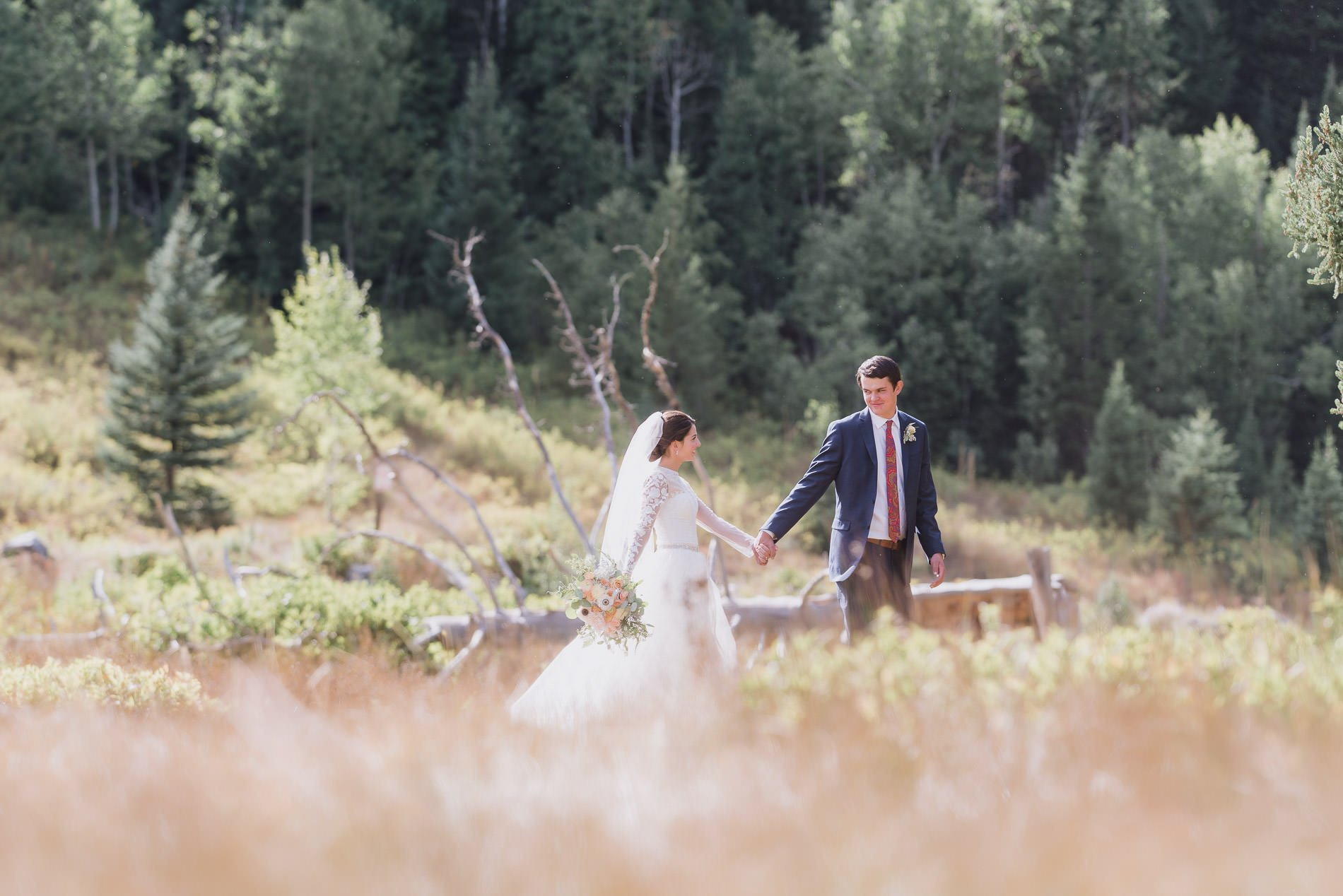 A groom leads a bride in the mountains for Utah bridal photography.