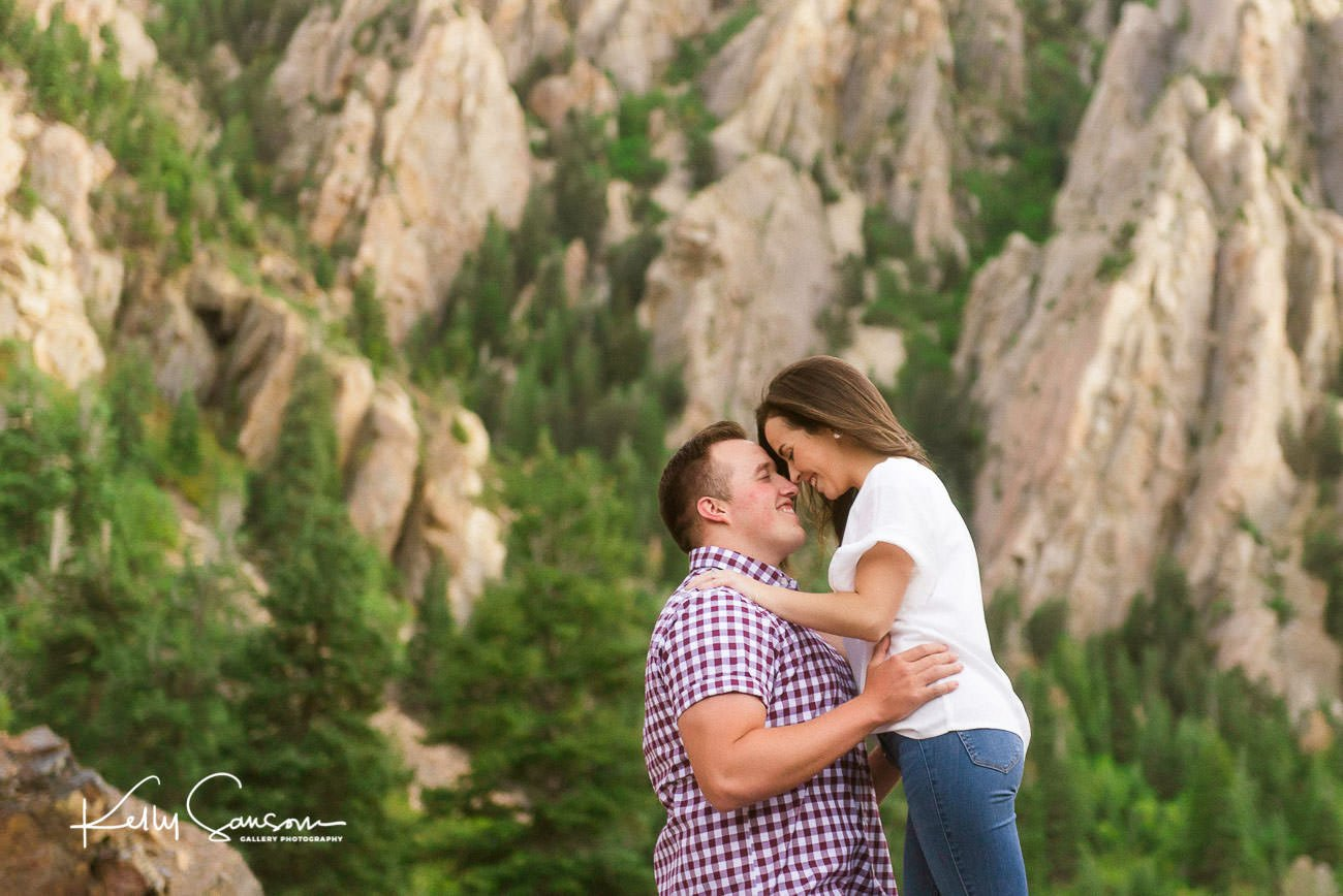 An engaged couple snuggling together in the mountains for Utah engagement photography.