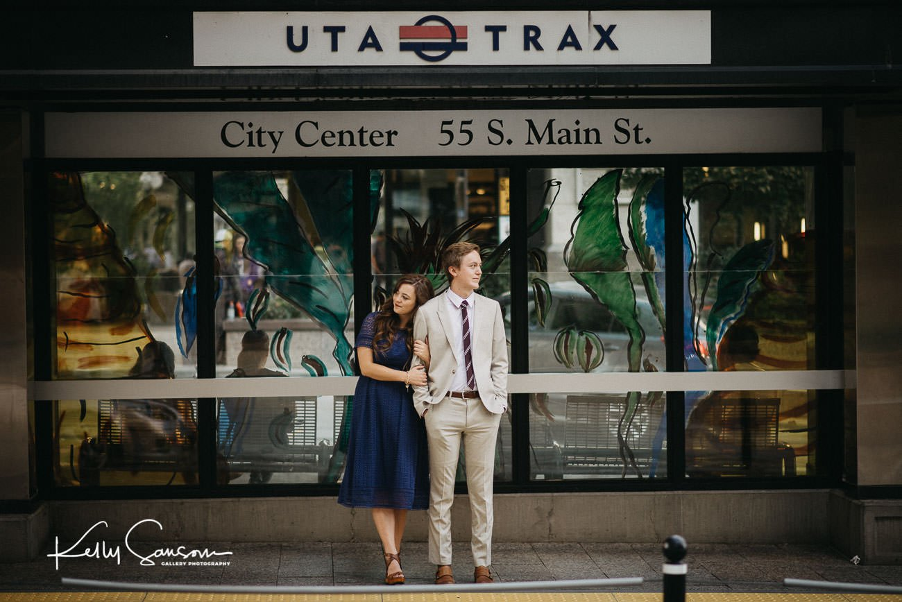 A couple standing waiting for a train at a UTA Trax station for Utah engagement photography.