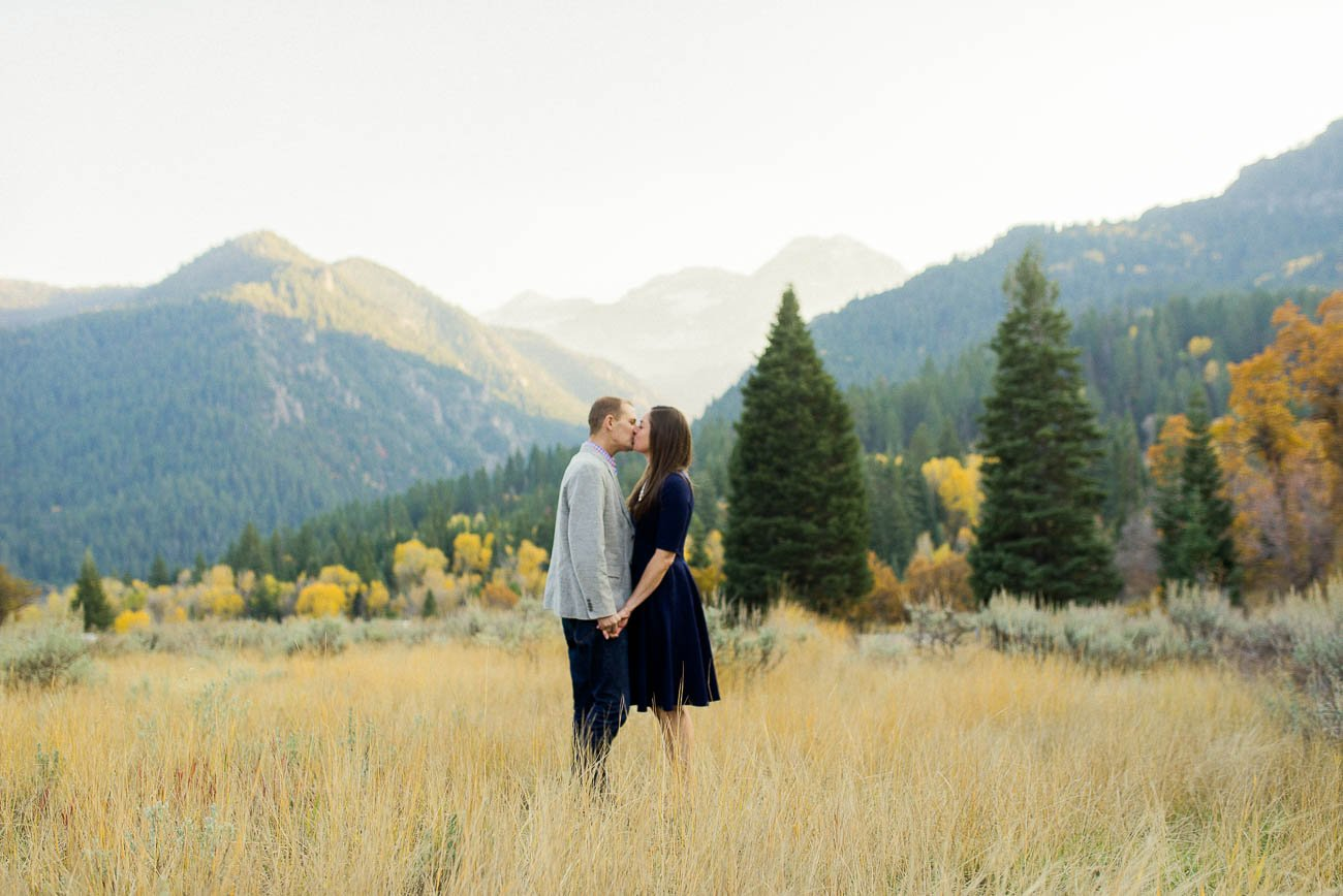 A couple kissing in tall grasses with Mount Tinpanogos behind them for Utah engagement photography.