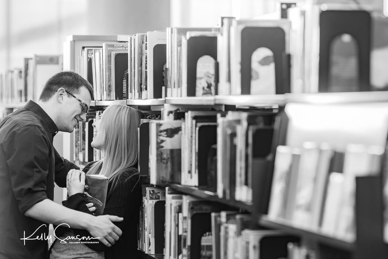 A couple snuggling together among books in the Salt Lake City Library for Utah engagement photography.