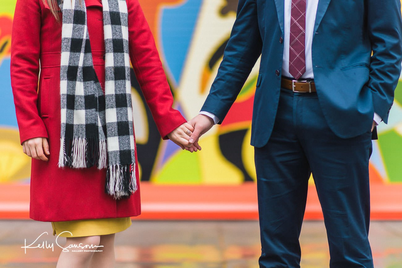 A couple holding hands in front of graffiti in downtown Salt Lake City for Utah engagement photography.