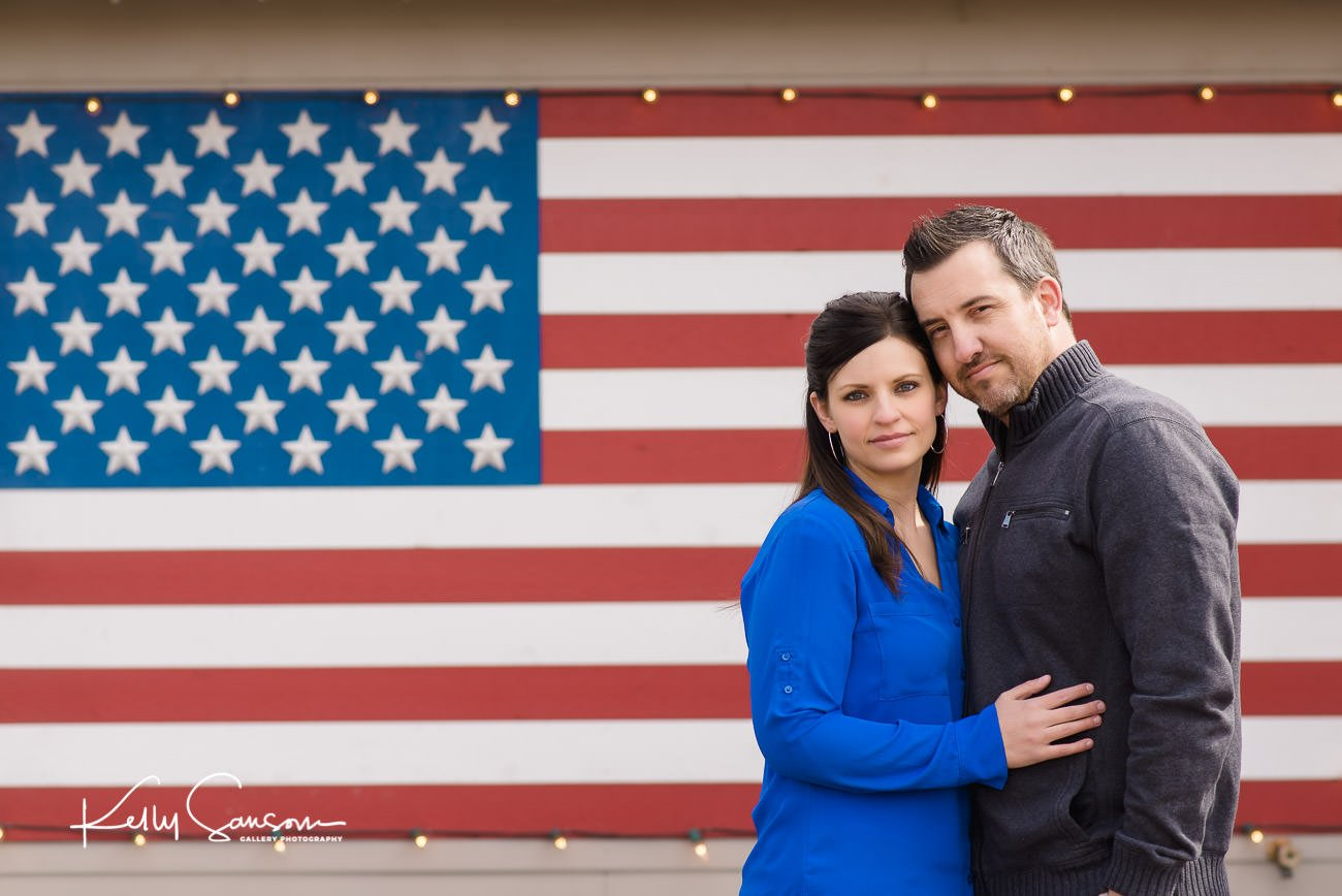 A couple snuggling together in front of a USA flag for Utah engagement photography.