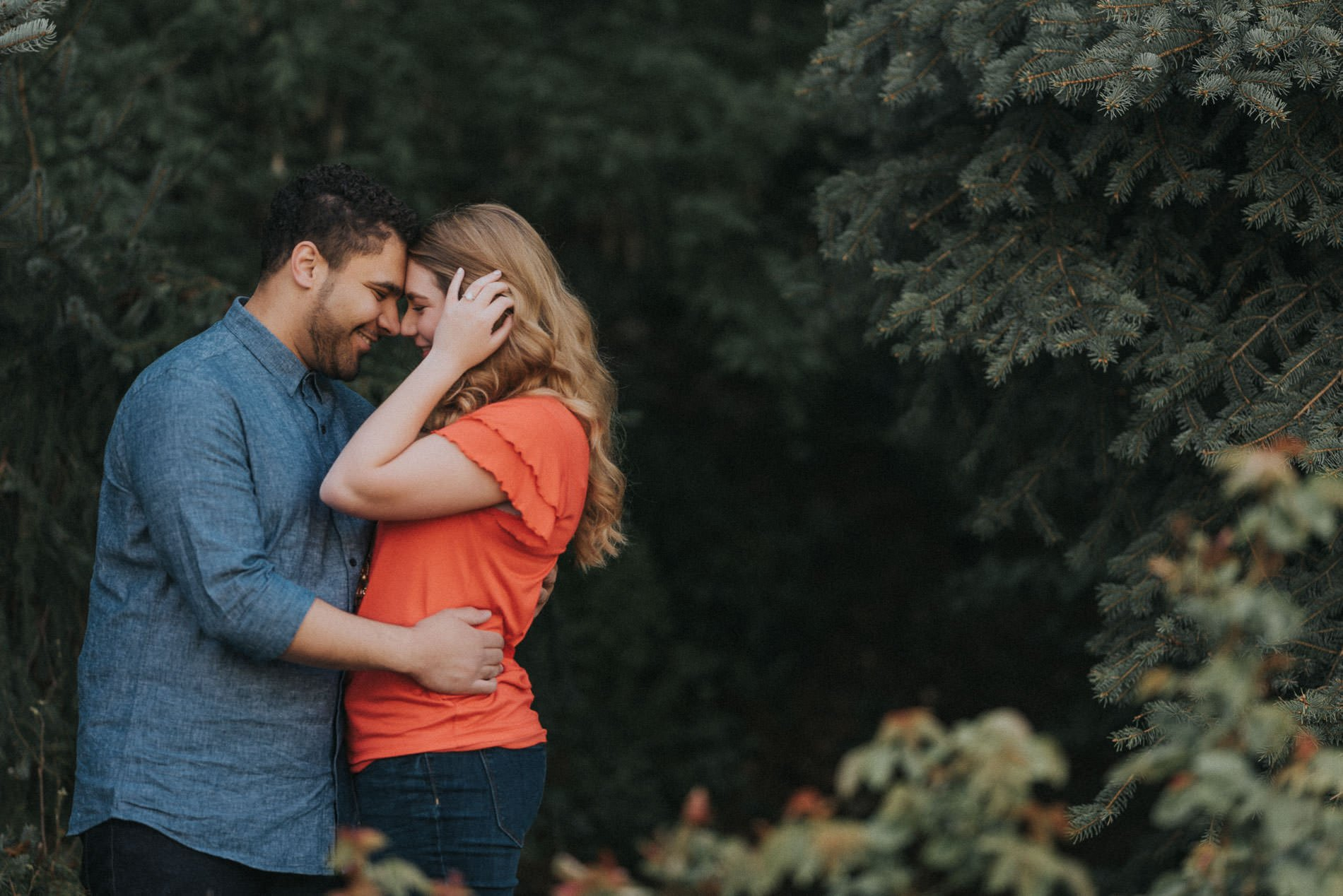 A couple touching foreheads in front of pine trees for Utah engagement photography.