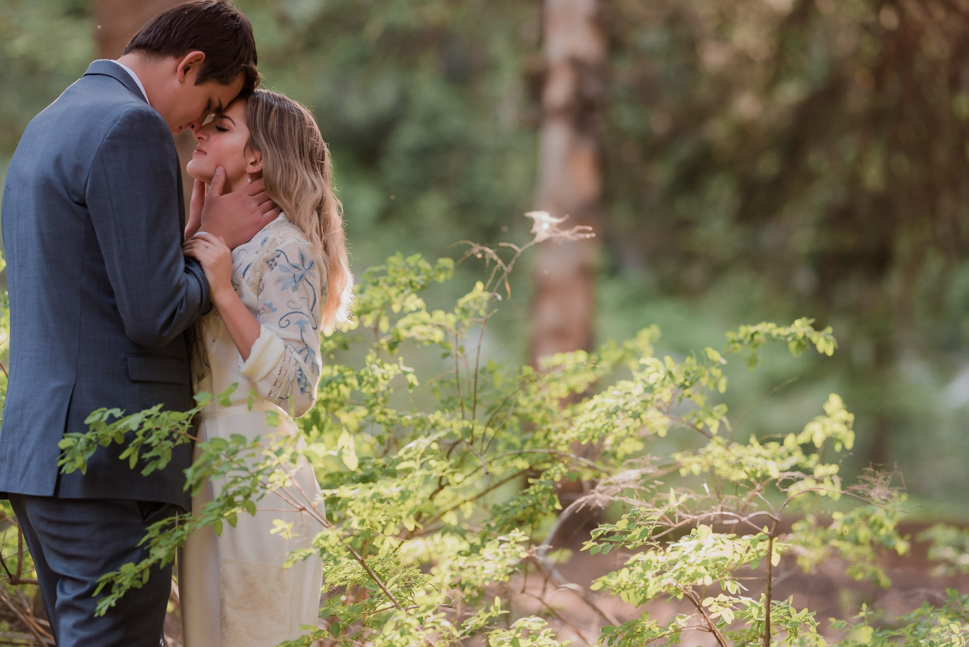 A man pulling a girls face close for a kiss among trees and bushes for Utah engagement photography.