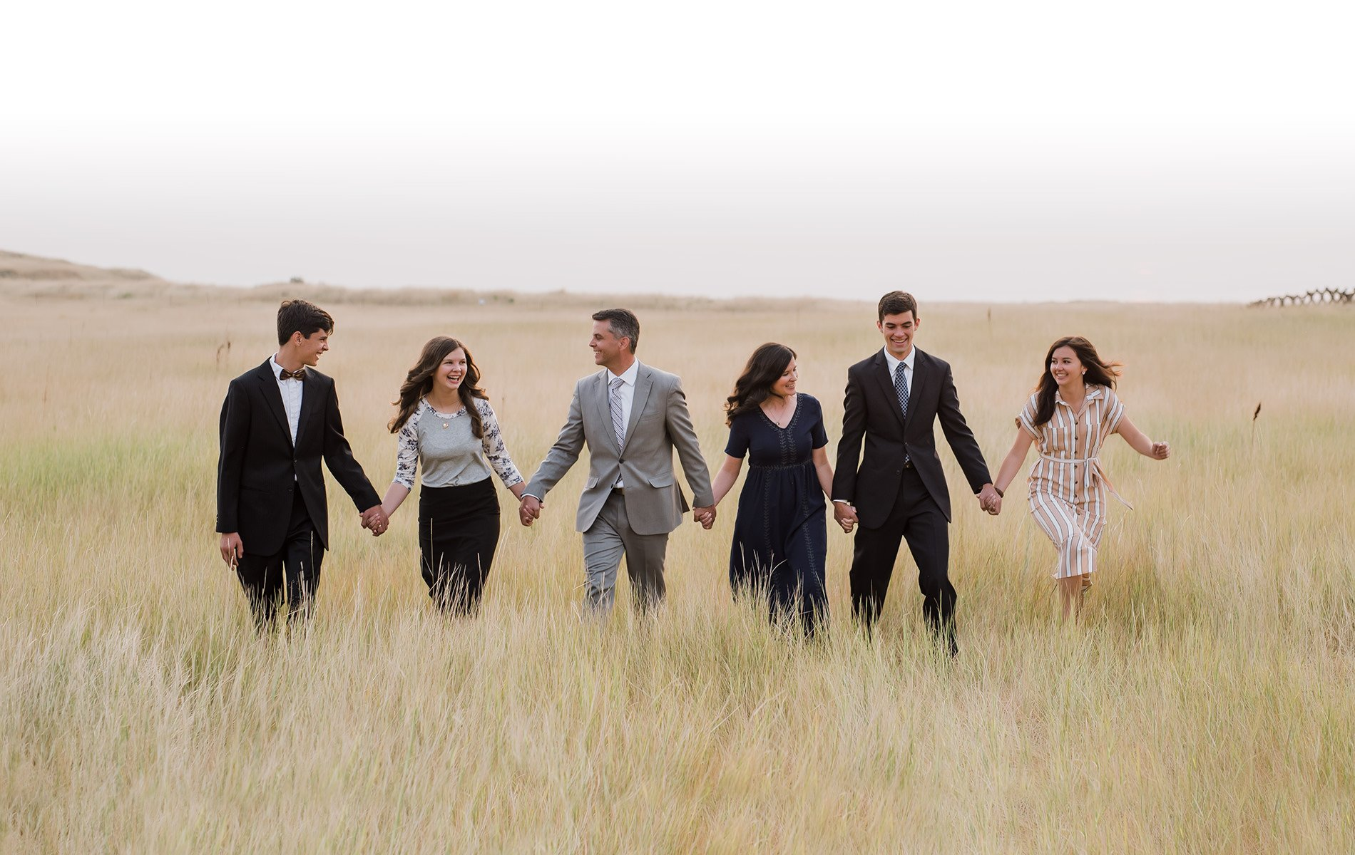 Family walking together in tall weeds for utah wedding and portrait photography.