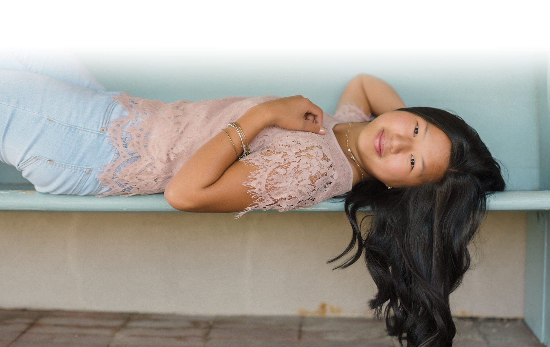 Girl laying on her back on a bench for Utah wedding and portrait photography.