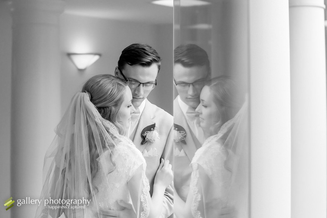 A bride and groom snuggling together by reflection from window at Bountiful LDS temple for Bountiful wedding Photography.