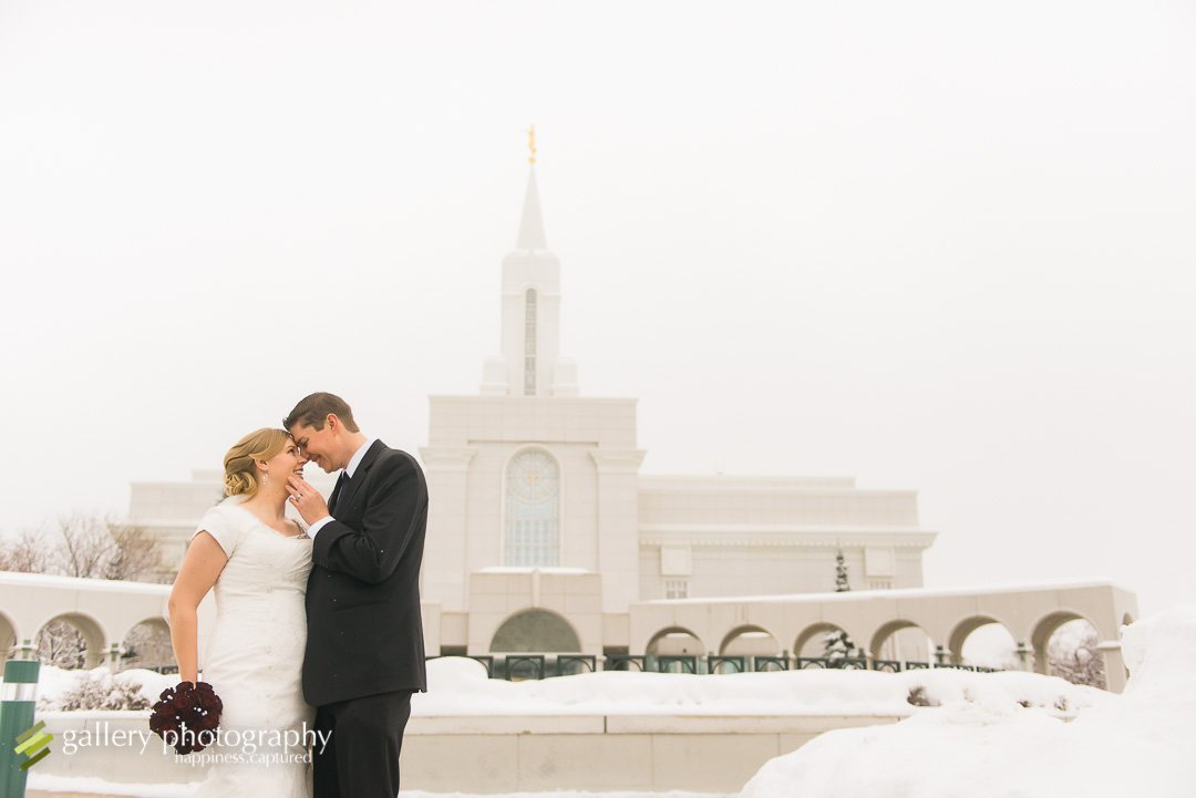 A couple touching foreheads on a snowy day in front of the Bountiful LDS temple for Bountiful wedding Photography.