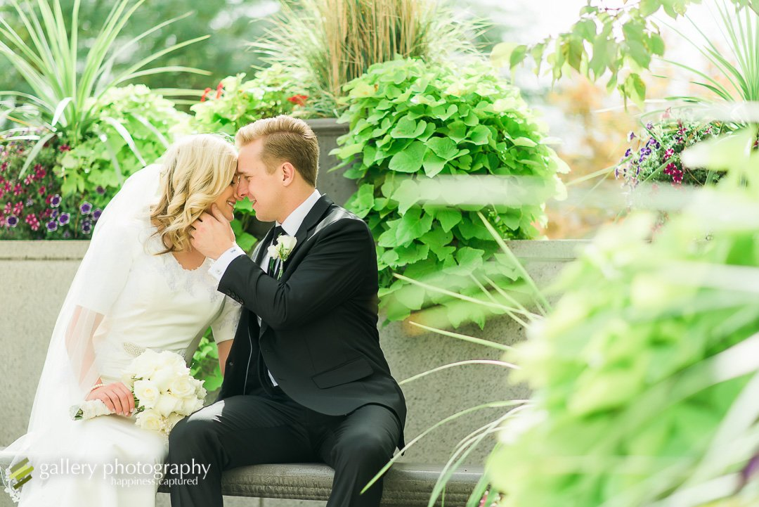 A groom touches a brides face as they snuggle on a bench for Bountiful wedding Photography.