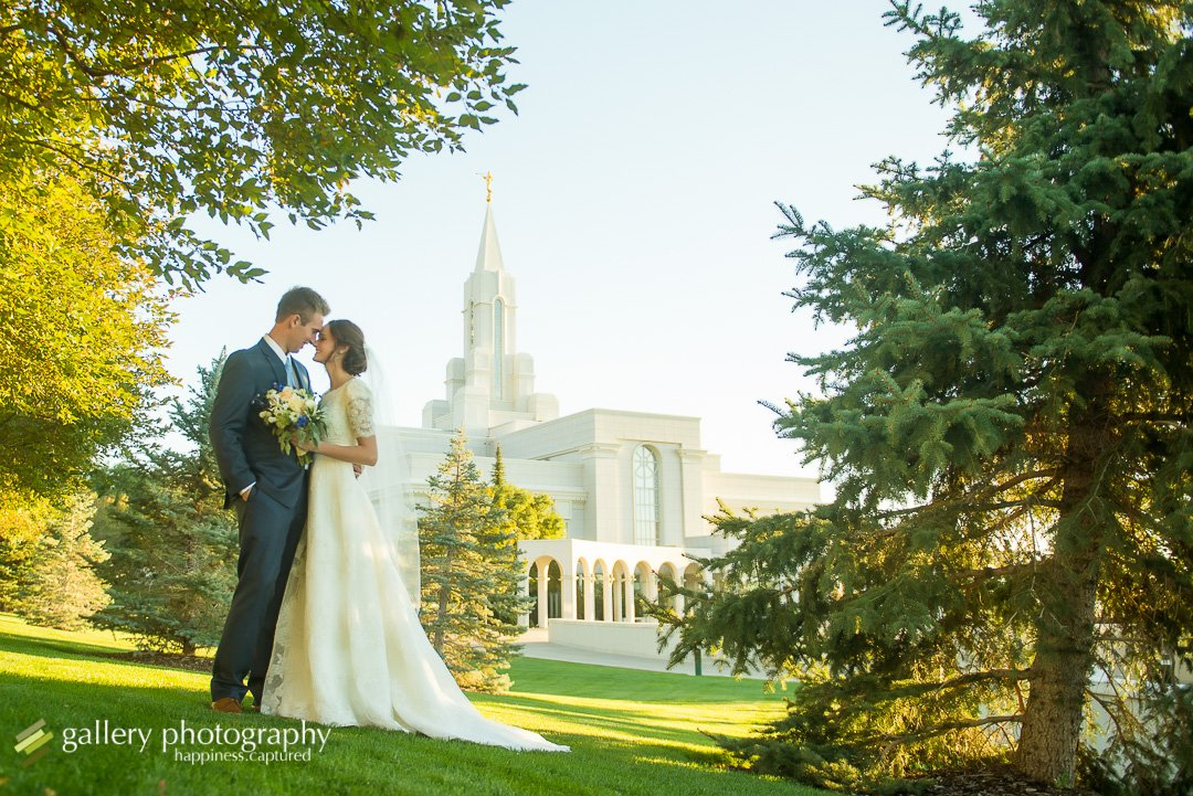 A couple snuggles touching heads in front of the Bountiful LDS temple for Bountiful wedding Photography.