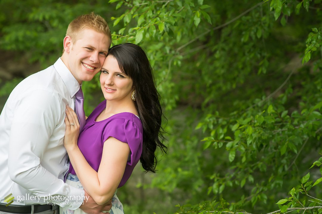 a young couple snuggling in nature in engagement photography at wheeler farm.