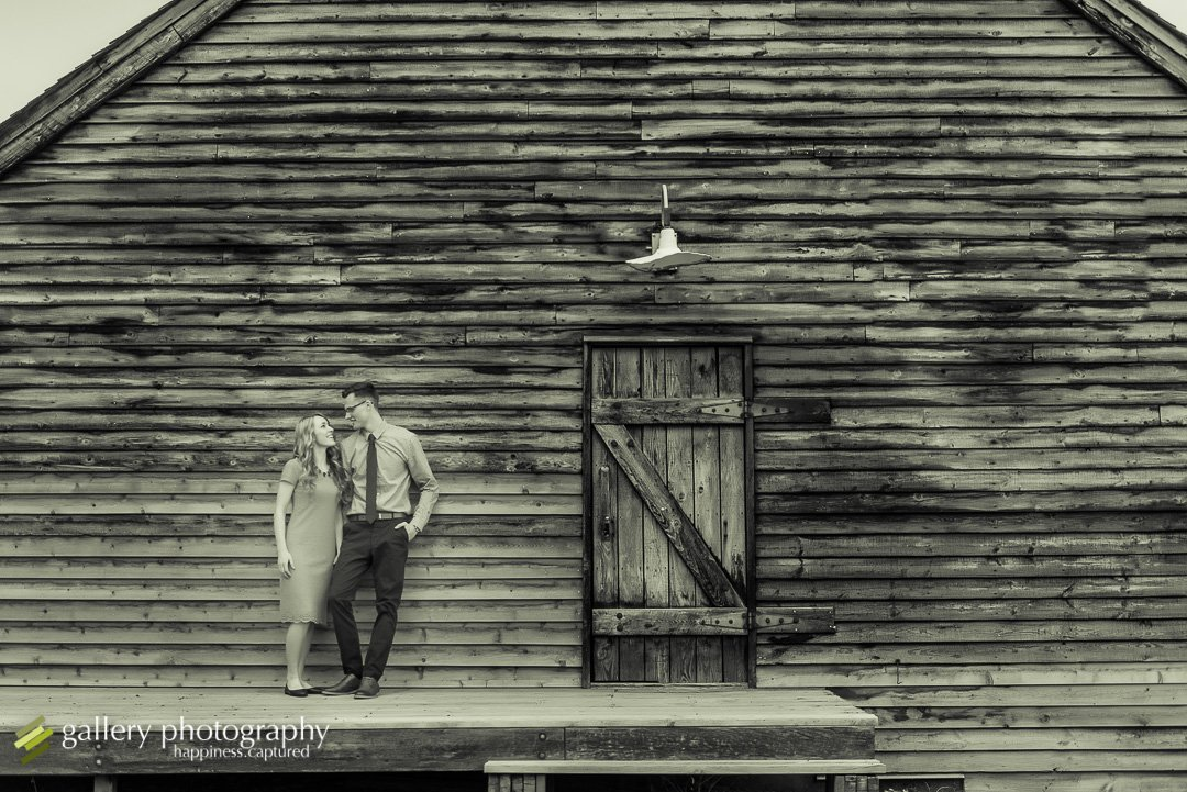 A couple snuggling against a rustic barn for engagement photography at Wheeler Farm.
