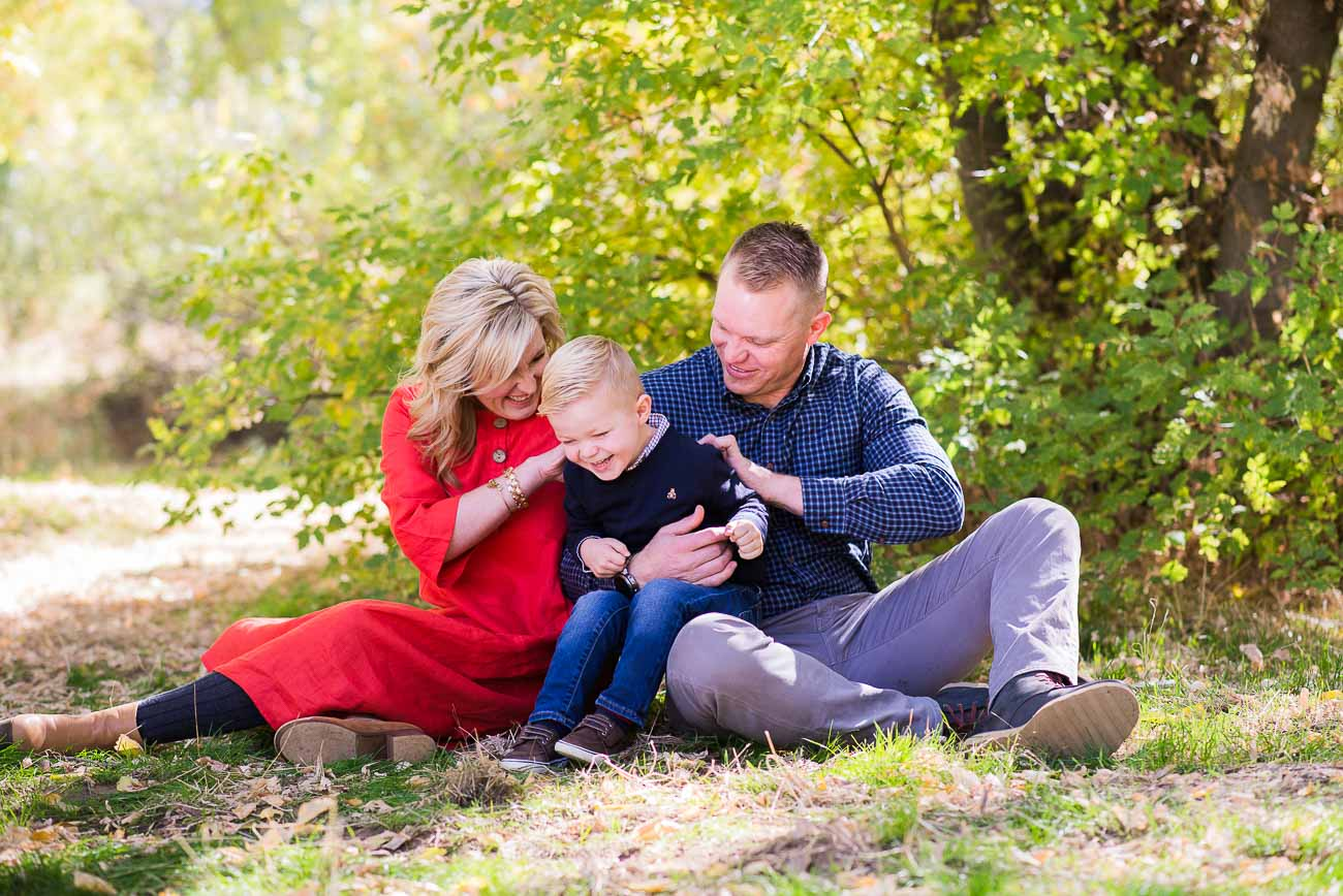 A couple tickling their young son for family photography at Wheeler Farm.