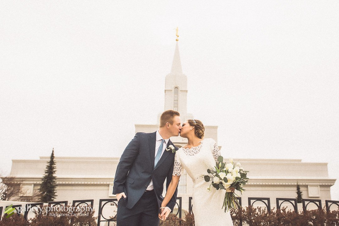 A bride and groom lean together and kiss for wedding photography at the Bountiful LDS temple.