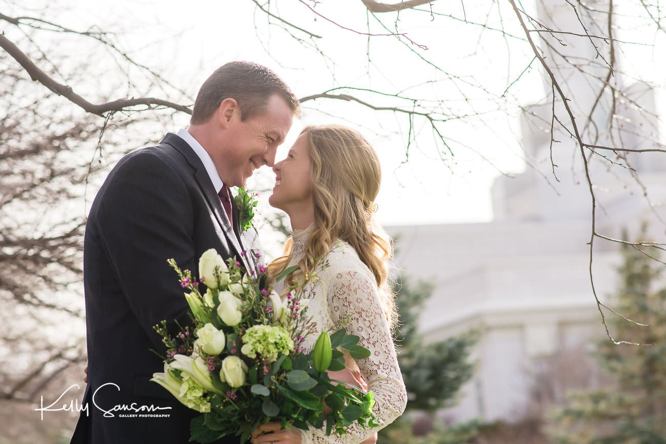 A bride and groom look at each other and smile for wedding photography at the Bountiful LDS temple.