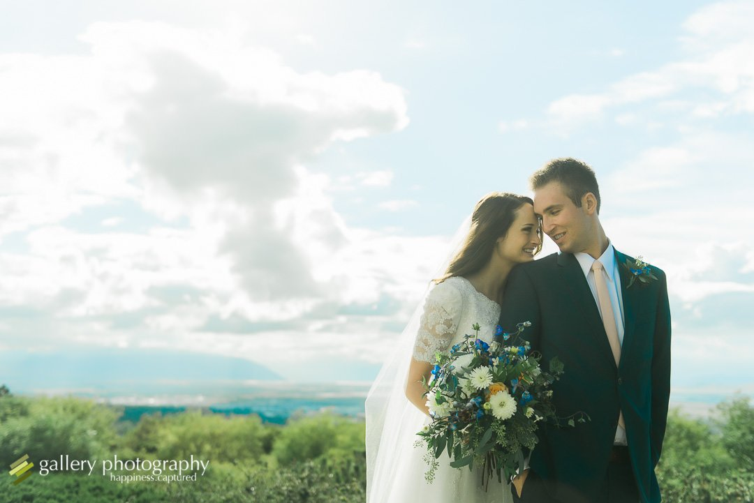 A bride and groom snuggle with a view of the valley below for wedding photography at the Bountiful LDS temple.