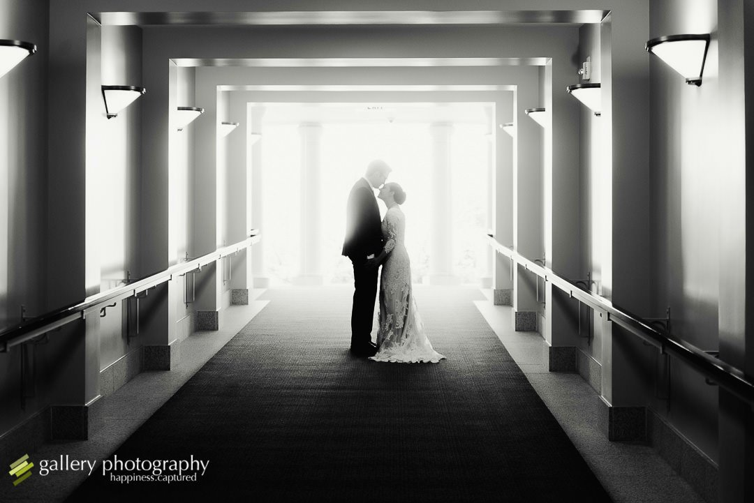 A bride and groom stop to cuddle in the hallway at the Bountiful LDS temple for wedding photography at the Bountiful LDS temple.