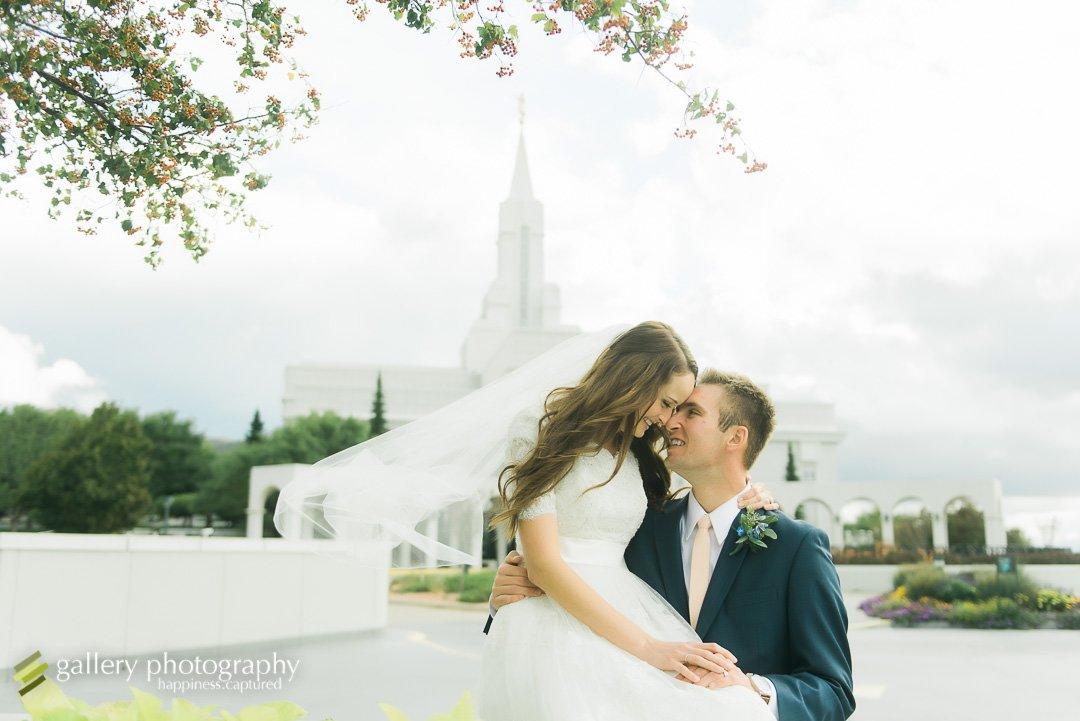 A bride sits on a bench and touches her grooms face for wedding photography at the Bountiful LDS temple.