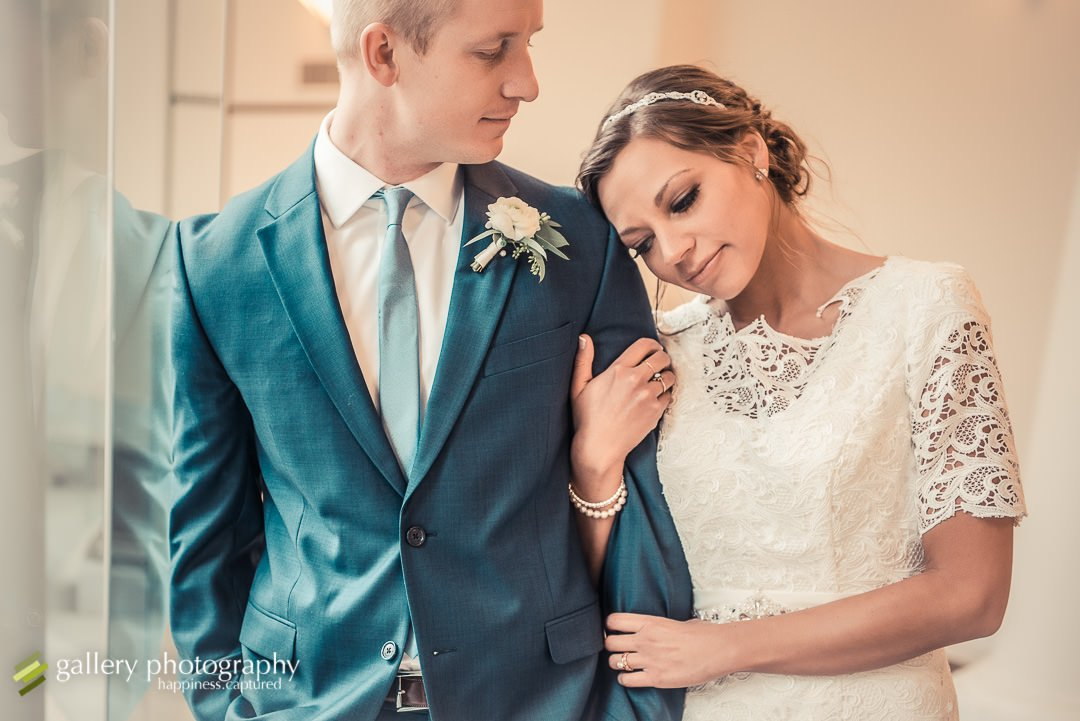 A bride leans on the shoulder of her groom for wedding photography at the Bountiful LDS temple.