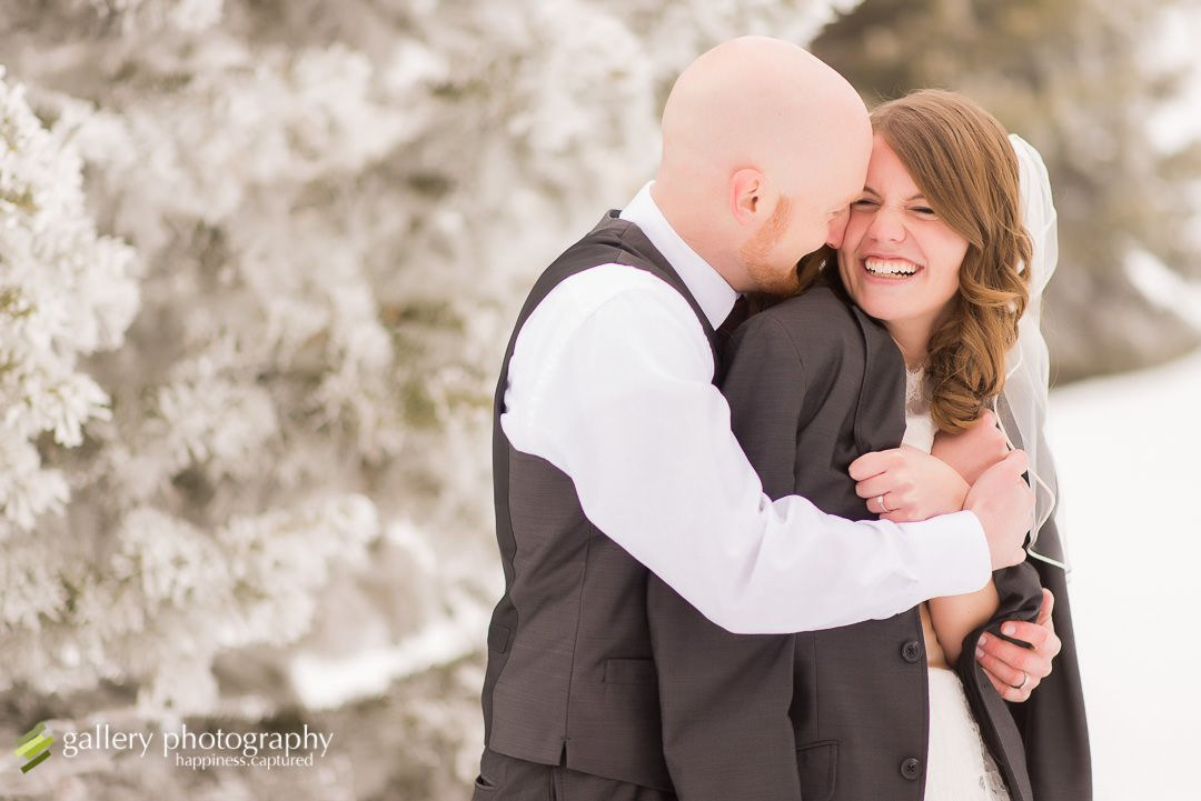 A groom wraps his coat around his bride in a snowy scene for wedding photography at the Bountiful LDS temple.