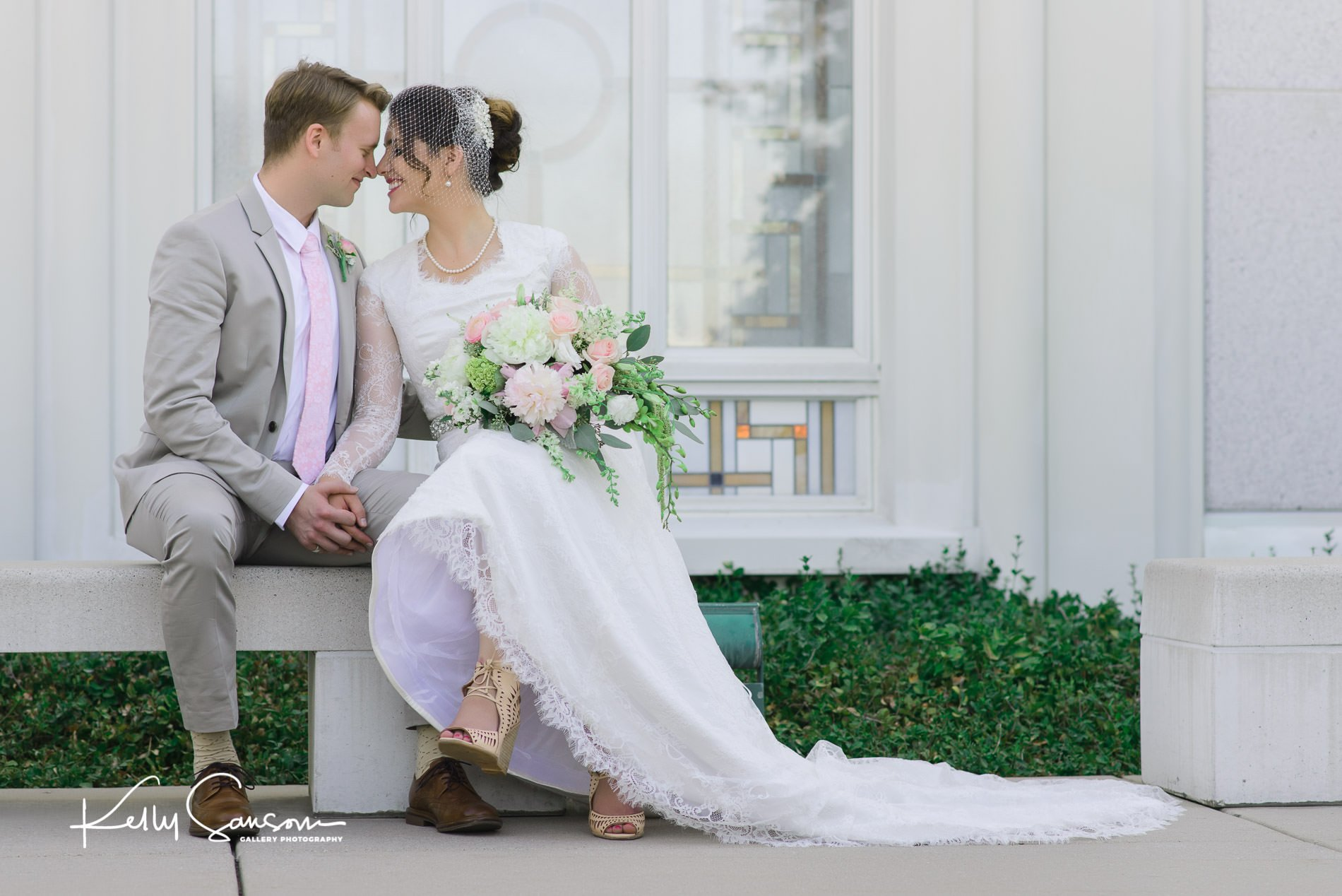 A bride and groom sit on a bench and touch foreheads for wedding photography at the Bountiful LDS temple.