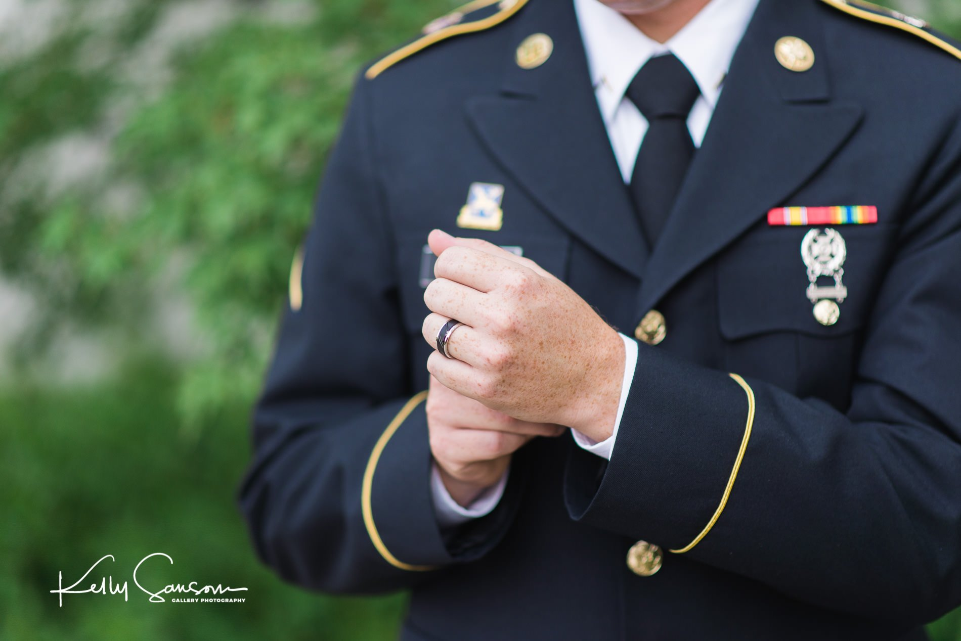 A groom in dress military straightens his cuff for wedding photography at the Bountiful LDS temple.